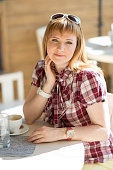 A girl sits at a table in a summer cafe near a large window with a cup of coffee. European white with blond hair. Vertical photo
