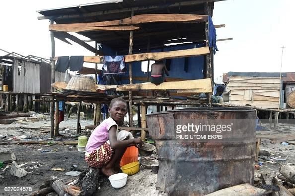 A girl sits in front of house shores at a makeshift home partly demolished at Otodo Gbame waterfront fishing communities in Lagos on November 28 2016...