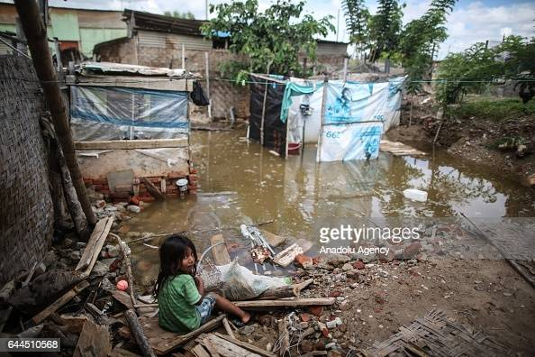 A girl sits near a flooded area after a heavy seasonal rainfall caused flood in Sullana Peru on February 23 2017 Peru has been hit this week by...