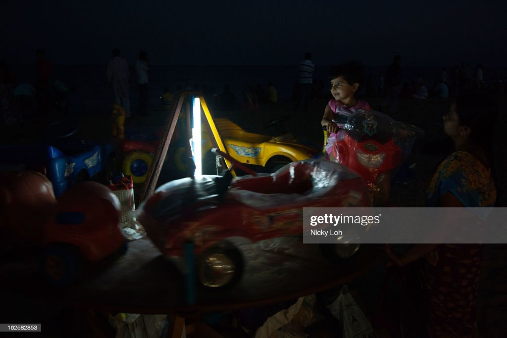 A girl sits on a ride at the Marina Beach on February 24, 2013 in Chennai, India. Marina Beach is an urban beach along the Bay of Bengal, which is part of the Indian Ocean. The beach runs a distance of 13km (8.1 miles), making it the longest natural urban beach in the country and the world's second longest.