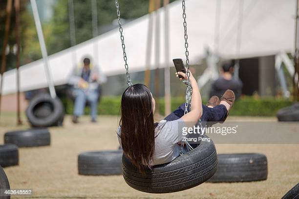 A girl sits on a swing taking selfies People take more selfies than ever before which becomes one of the hottest topics nowadays