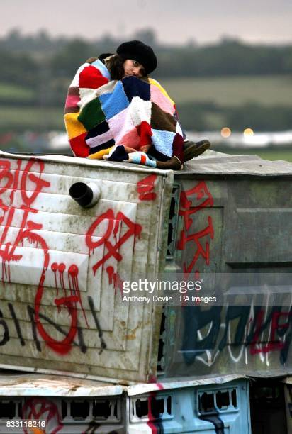 A girl sits on an installation by the artist Banksy as festival goers celebrate the mid summer solstice at the Glastonbury Festival at Worthy Farm in...