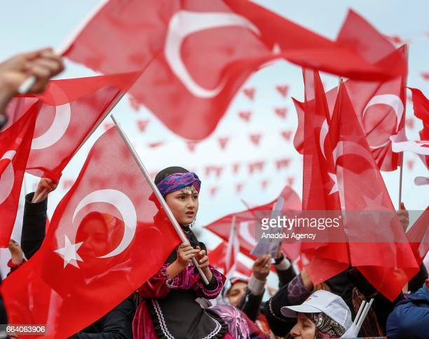 A girl sits on her mother's shoulders as people gather to listen Turkish President Recep Tayyip Erdogan's speech during a mass opening ceremony in...