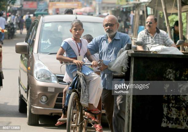 A girl sits on the handle bar of a bicycle as she is going to her school to studying by the help of her grand father in the eastern Indian state...