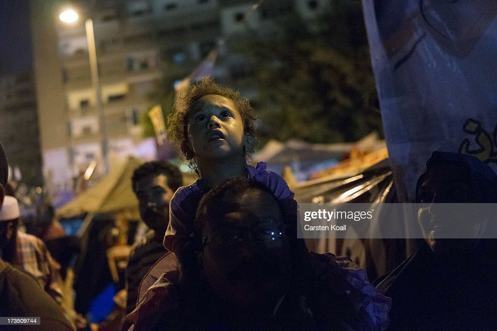 A girl sits on the shoulders of a man as members of the Muslim Brotherhood and supporters of ousted president Mohamed Morsi hold a rally outside Rabaa al-Adawiya mosque on July 15, 2013 in Cairo, Egypt. Senior US official William Burns has arrived in Egypt for the first time since the overthrow of Mohamed Morsi.