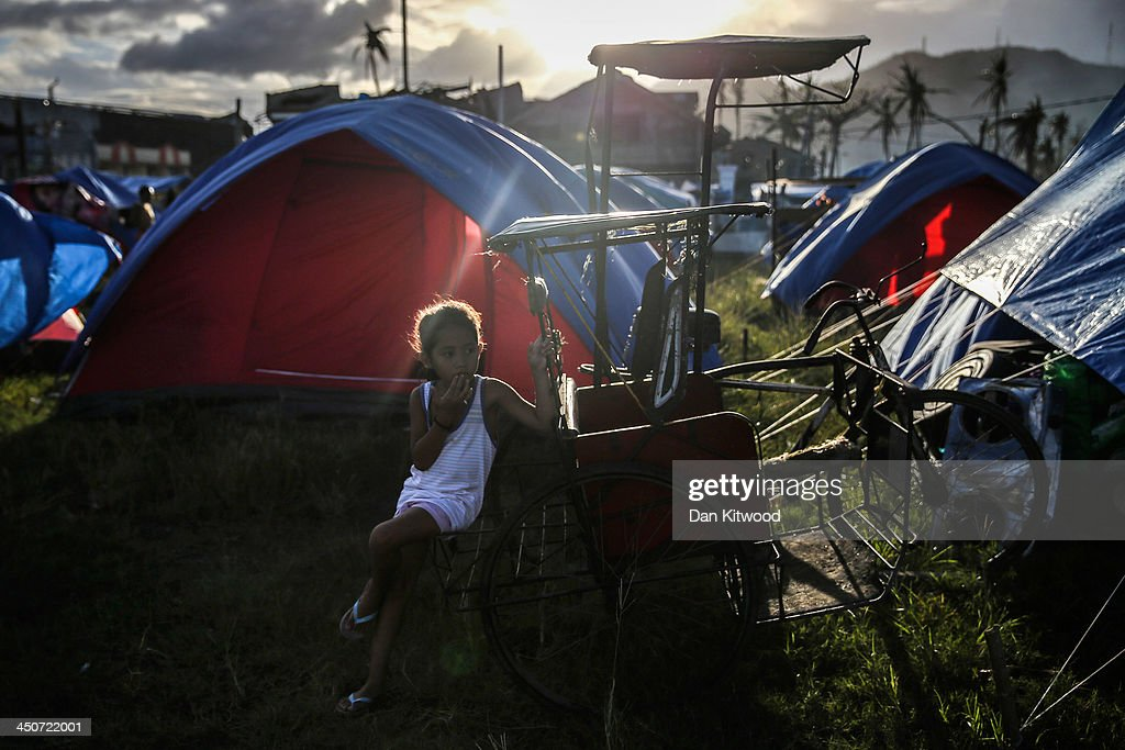 A girl sits outside her tent at the Tacloban astrodome evactuatuion centre on November 20 2013 in Leyte Philippines Typhoon Haiyan which ripped...