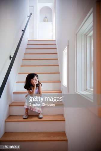 girl sits quietly in light-filled stairwell : Stock Photo