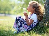 Girl (5-7) sitting against tree, blowing dandelion, profile