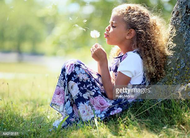 Girl (5-7) sitting against tree, blowing dandelion, profile