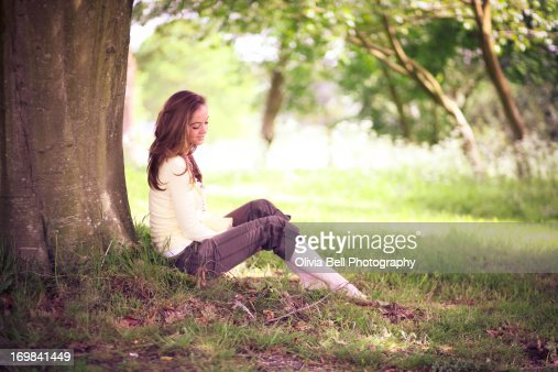 Girl sitting against tree in spring