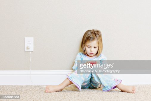 Girl Sitting Against Wall Playing on a Smart Phone
