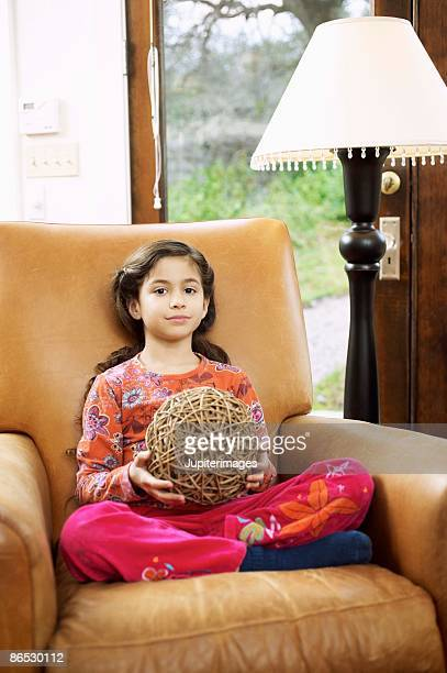 Girl sitting and holding ball of rubber bands