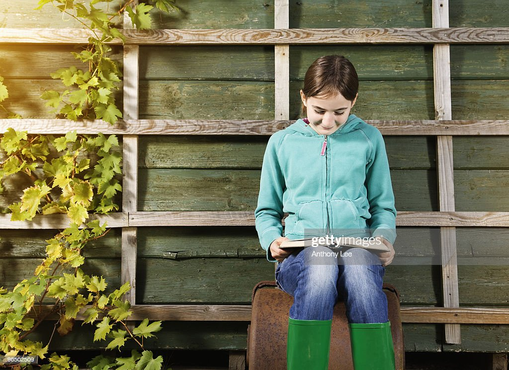 Girl sitting and reading book near vine : Stock Photo