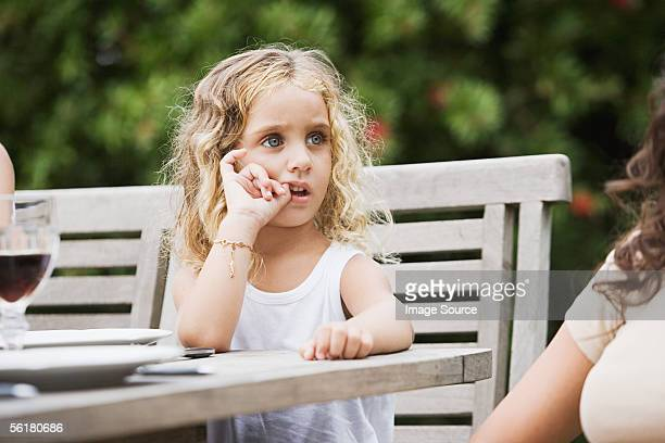 Girl sitting at a table outside