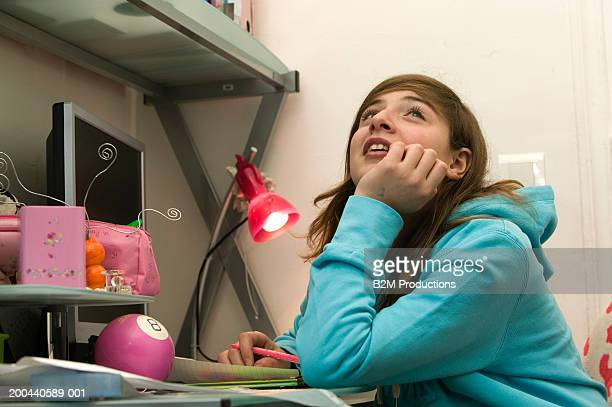 Girl (11-13) sitting at desk, resting chin on hand, low angle view