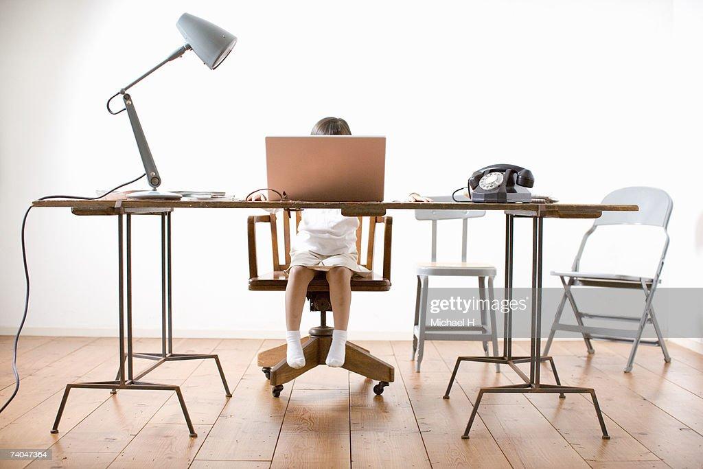 Girl (6-7) sitting at desk, using laptop