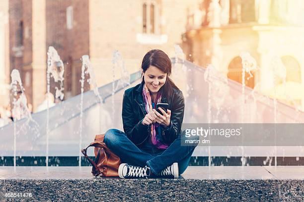 Mädchen sitzt am Brunnen und er ein smartphone benutzt