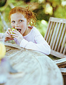 Girl (6-8) sitting at garden table eating fruit (focus on girl)