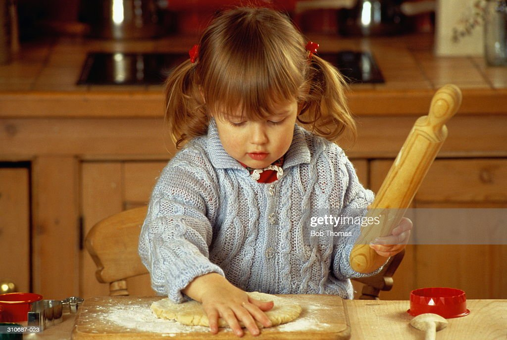 Girl(3)sitting at kitchen table rolling out pastry dough : Stock Photo