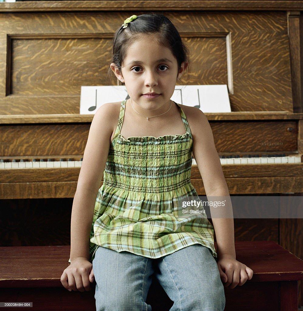 Girl (4-6) sitting at piano, portrait : Stock Photo