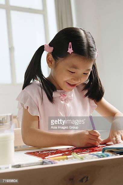 Girl sitting at table, drawing
