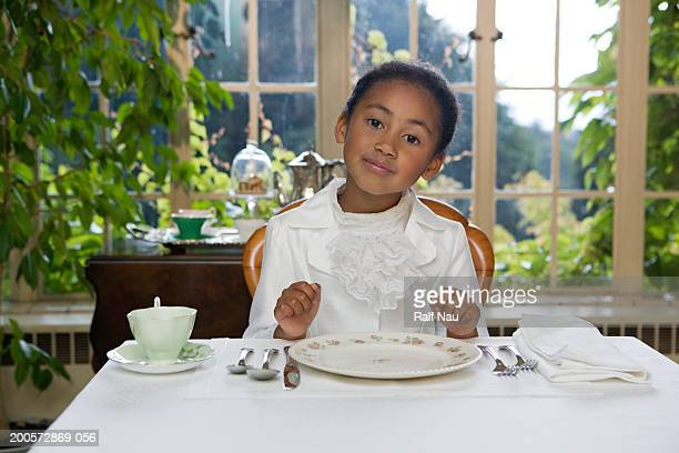 Girl (5-7) sitting at table setting, smiling