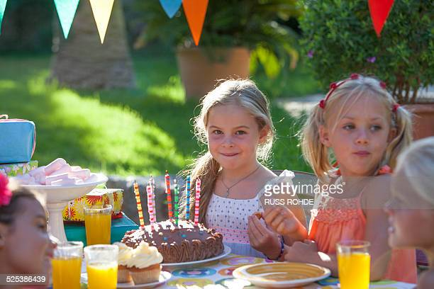 Girl sitting at table with birthday cake