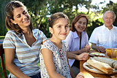Girl (6-7) sitting at table with family, smiling