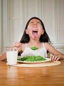 Girl (8-9) sitting at table with plate of green peas, sticking out tongue