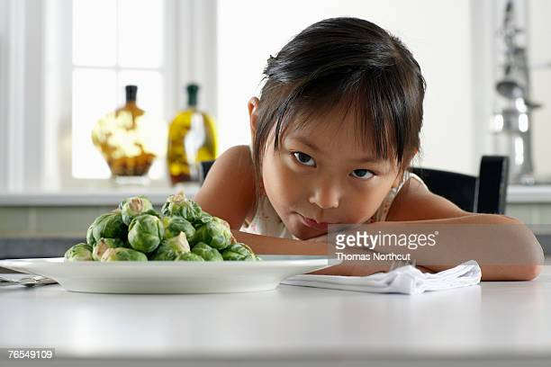 Girl (3-5) sitting at table with plate of sprouts, portrait