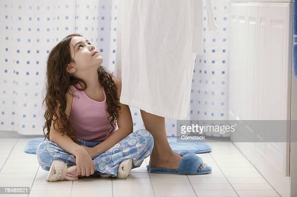 Girl sitting below mother in bathroom