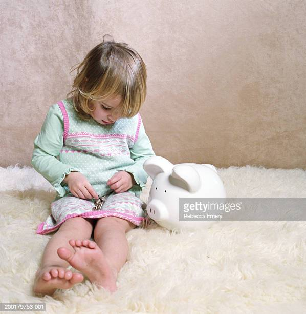 Girl (2-4) sitting beside piggy bank, looking down at coins on lap