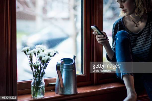 A girl sitting by a window and looking at her cellphone