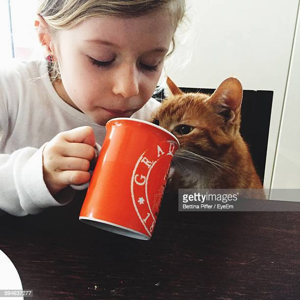 Girl Sitting By Cat At Home