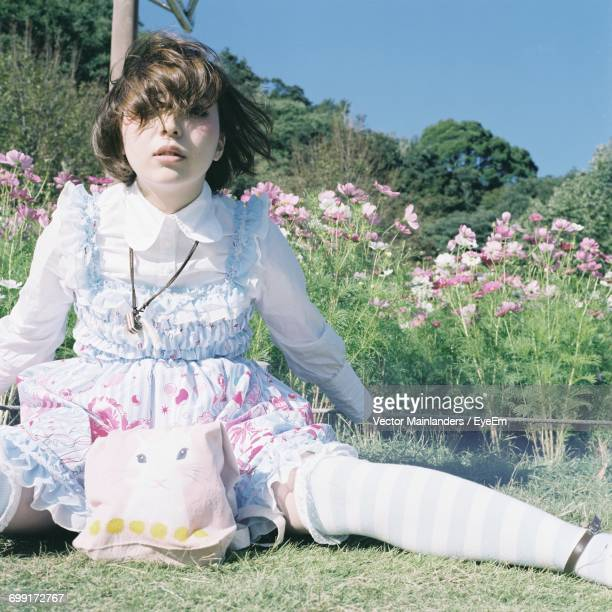 Girl Sitting By Flowers On Field