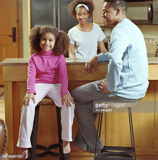 Girl (6-8) sitting by parents in kitchen, smiling, portrait