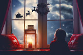 Merry Christmas and happy holidays! Cute little child girl sitting by window and looking at Santa Claus flying in his sleigh against moon sky. Room decorated on Christmas. Kid enjoy the holiday.