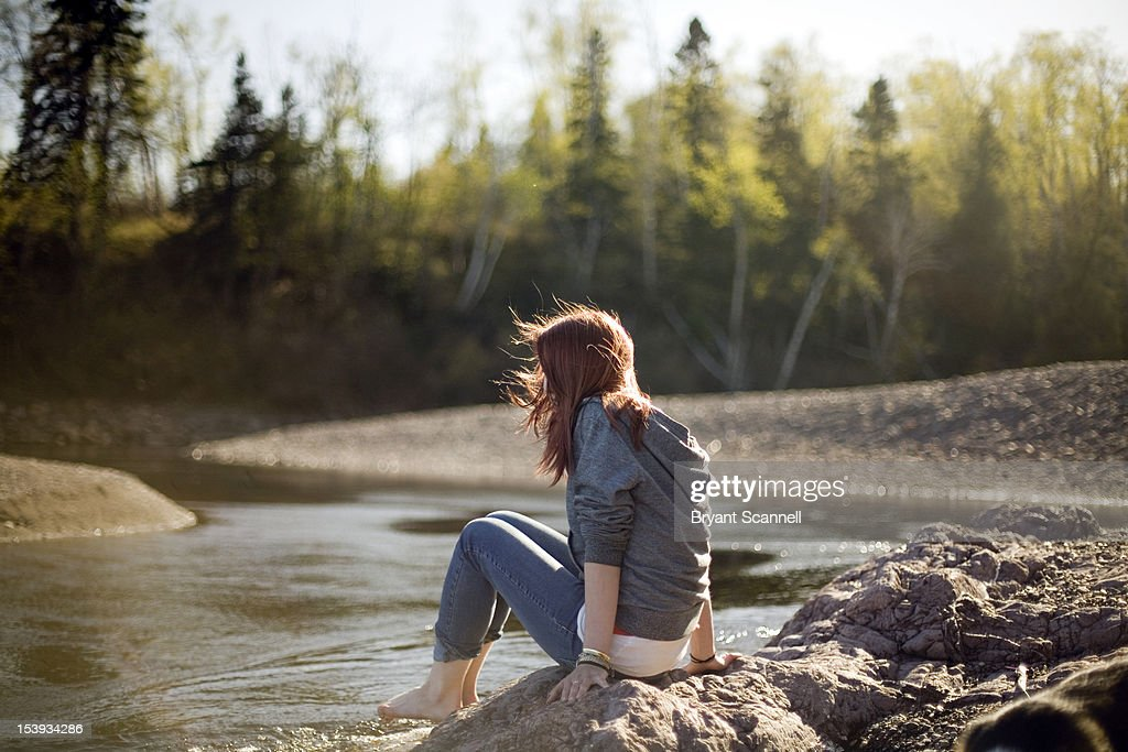 Girl sitting by water : Stock Photo