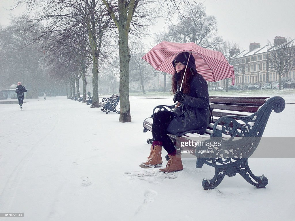 Girl sitting in a bench on a snowy day