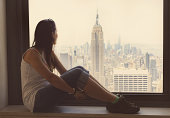 Girl sitting in a window looking views of New York