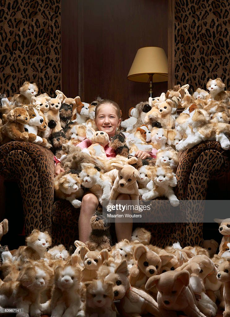 Girl sitting in an armchair full of stuffed toys : Stock Photo