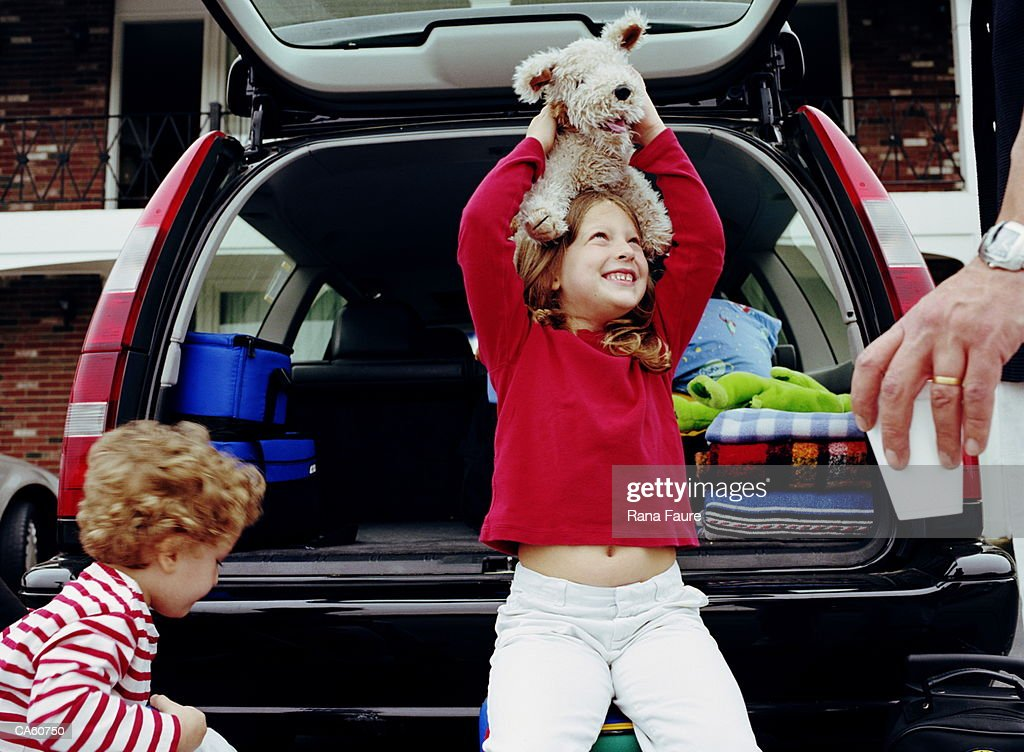 Girl (6-8) sitting in back of station wagon with stuffed dog : Stock Photo
