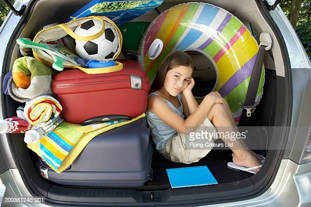 Girl (8-10) sitting in boot of car amongst luggage, portrait