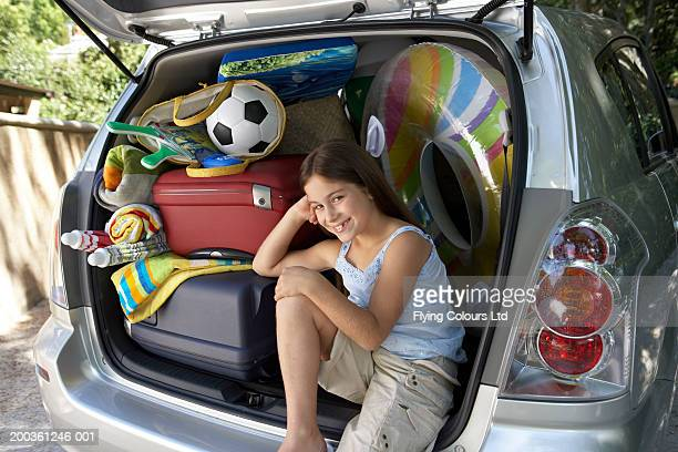 Girl (8-10) sitting in boot of car amongst luggage, smiling portrait