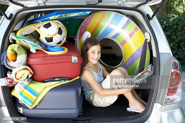 Girl (8-10) sitting in boot of car holsing book, smiling, portrait