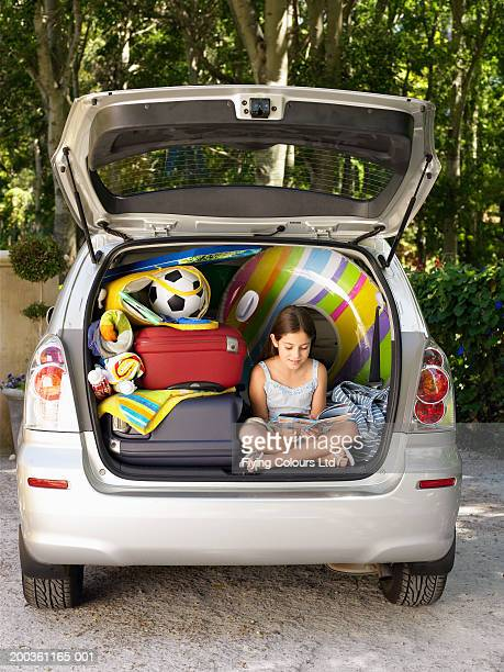 Girl (8-10) sitting in boot of car reading amongst luggage