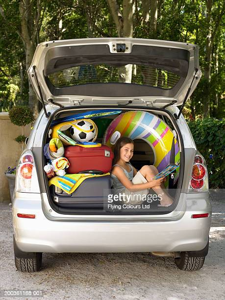 Girl (8-10) sitting in boot of car reading amongst luggage, portrait