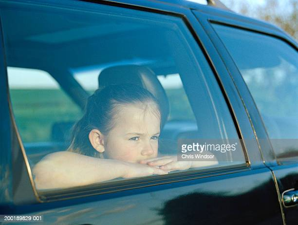 Girl (7-9) sitting in car, looking out window, view through window