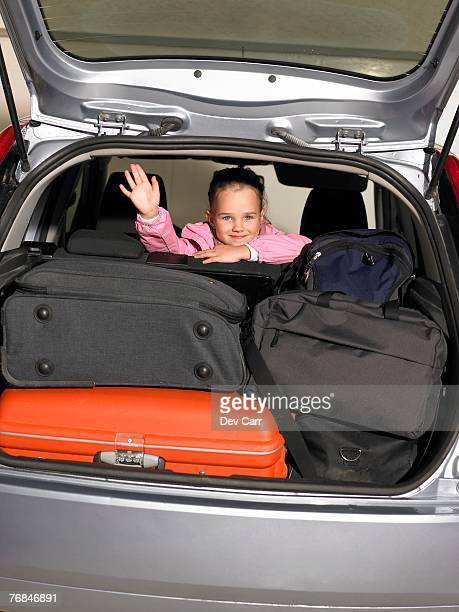 Girl (5-7) sitting in car with luggage, waving