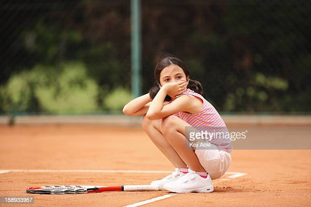 Girl Sitting In Clay Court